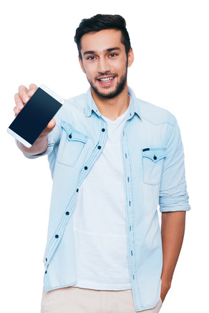 showing: Look at my new smart phone! Handsome young Indian man showing his smart phone and smiling while standing against white background Stock Photo