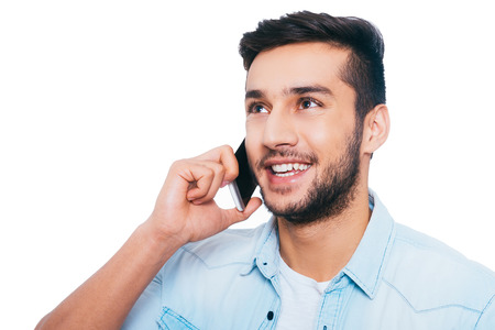 men talking: Good talk with friend. Handsome young Indian man talking on the mobile phone and smiling while standing against white background Stock Photo