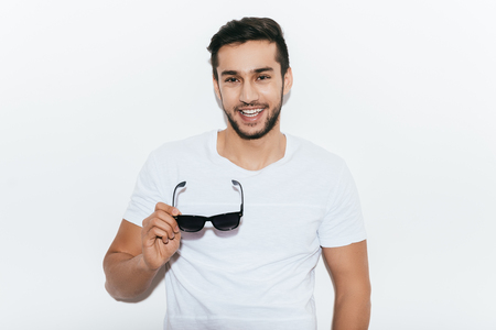 heartbreaker: Charming heartbreaker. Handsome young Indian man carrying sunglasses and looking at camera with smile while standing against white background