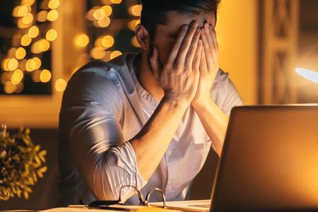 agotado: Sentirse enfermo y cansado. Hombre joven frustrado que cubre la cara con las manos mientras está sentado en su lugar de trabajo en la noche con las luces de Navidad en el fondo Foto de archivo