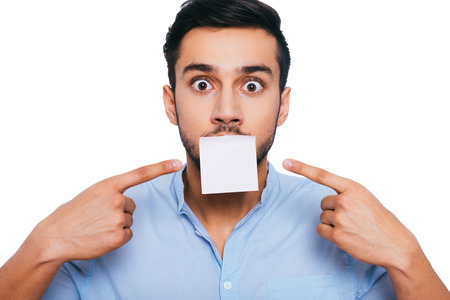 adhesive note: I have nothing to say except this... Shocked young Indian man pointing adhesive note on his mouth and staring at you while standing against white background Stock Photo