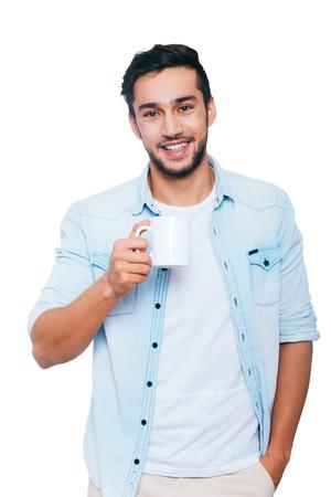 hombres jovenes: Tomando un descanso para tomar café. apuesto joven indio que sostiene la taza de café y sonríe mientras está de pie contra el fondo blanco