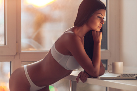 woman nude standing: Surfing the net at home. Beautiful young woman in white lingerie holing hand on chin and looking at her laptop while standing near the window at home