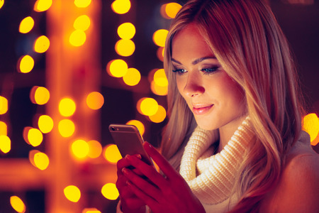 to get warm: Typing lovely message to him. Beautiful young smiling woman in white sweater holding smart phone and looking at it with defocused Christmas lights in the background