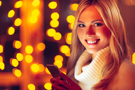 to get warm: Always in touch with her nearest. Beautiful young smiling woman in white sweater holding smart phone and looking at camera with defocused Christmas lights in the background
