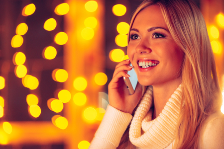 to get warm: Staying connected. Beautiful young smiling woman in white sweater talking on the mobile phone with defocused Christmas lights in the background Stock Photo