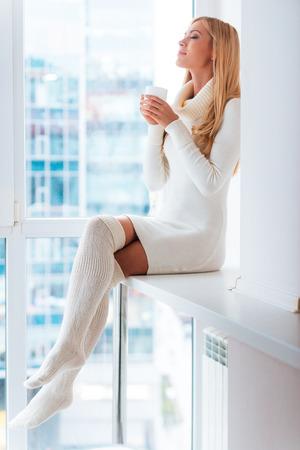 mujer desnuda sentada: Comer bien el día en casa. mujer de pelo rubio joven en suéter caliente y medias disfrutando de café y mantener los ojos cerrados mientras se está sentado en frente de la ventana en el país