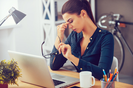 women only: Feeling tired and stressed. Frustrated young woman keeping eyes closed and massaging nose while sitting at her working place in office