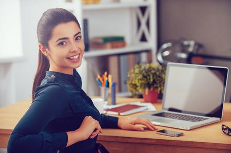 Těší její pracovní den. Atraktivní mladá žena dívá přes rameno a usmívá zatímco sedí u svého pracovního místa v kanceláři