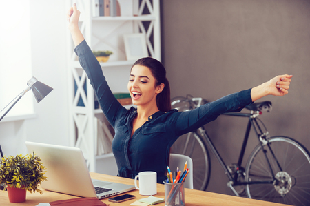 Winning every day. Attractive young woman stretching out hands and looking excited while sitting at her working place and looking at laptop
