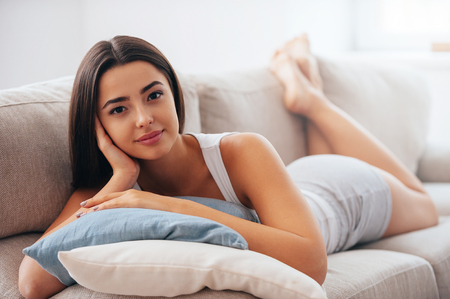 woman resting: Enjoying leisure time at home. Beautiful young woman holding hand on hair and looking at camera while lying on the couch at home