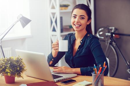 휴식 시간. 사무실에서 그녀의 작업 장소에 앉아있는 동안 매력적인 젊은 여자 커피 잔을 들고 웃