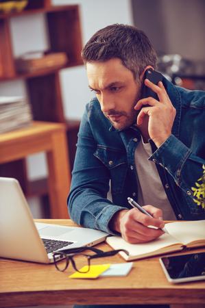 hombres jovenes: La concentración plena. Seguro de joven que trabaja en la computadora portátil y hablando por el teléfono móvil mientras se está sentado en su lugar de trabajo en la oficina