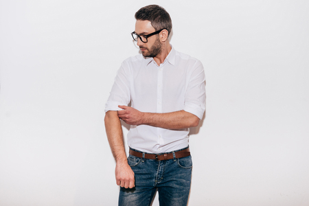 adjusting: Ready to work. Confident mature man in white shirt adjusting his sleeve while standing against white background Stock Photo