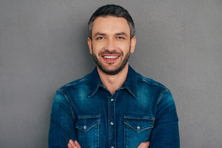 thirties: Cheerful handsome. Confident mature man in jeans shirt keeping arms crossed and smiling while standing against grey background