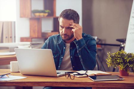 仕事の完全な集中力。自信を持って若い男がオフィスに彼の職場で座っている間のラップトップに取り組んで