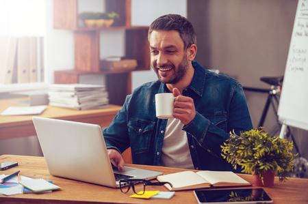 Inspirado com chávena de café fresco. Homem novo confiável que trabalha no portátil e que prende o copo de café enquanto está sentado em seu lugar de trabalho no escritório