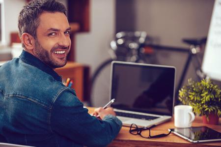 Gutes Arbeitstag. Rückansicht des selbstbewusster junger Mann sucht über die Schulter und lächelt, während sitzt an seinem Arbeitsplatz im Büro