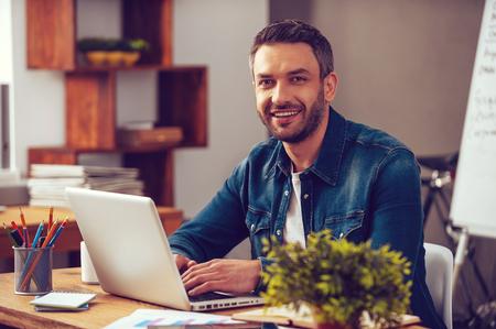 Confiante e bem sucedida. Homem novo confiável que trabalha no portátil e que sorri ao sentar-se no seu local de trabalho no escritório