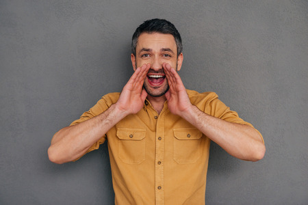 one mature man only: Sharing good news. Happy mature man holding hands around mouth and shouting while standing against grey background