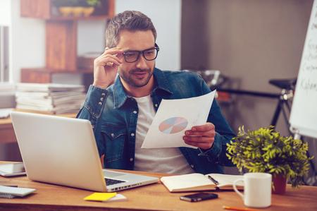 Nous montrons de bons résultats! Beau jeune homme papier avec diagramme coloré tenant et regardant ce alors qu'il était assis sur son lieu de travail dans le bureau