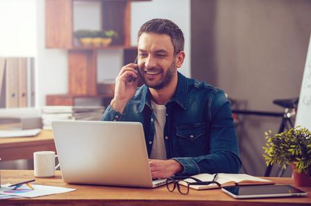 Njuter av god arbetsdag. Självsäker ung man som arbetar på en bärbar dator och pratar i mobiltelefon samtidigt som sitter vid sin arbetsplats i office Stockfoto