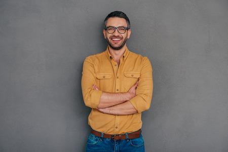 confianza: Seguro y exitoso. Hombre maduro confidente que sostiene la mano en la barbilla y mirando a cámara con una sonrisa mientras está de pie contra el fondo gris