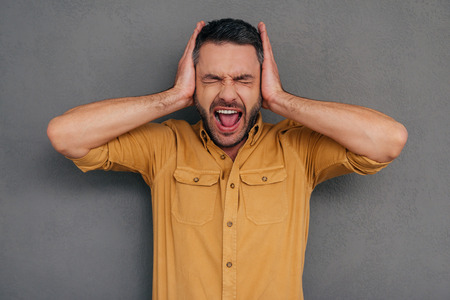 hands covering ears: Too loud sound! Furious mature man covering ears with hands and shouting while standing against grey background