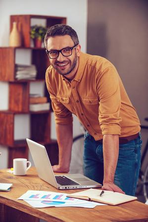 Ficar positivo em qualquer situação. Homem novo considerável olhando para câmera e sorrindo ao estar perto de seu local de trabalho no escritório