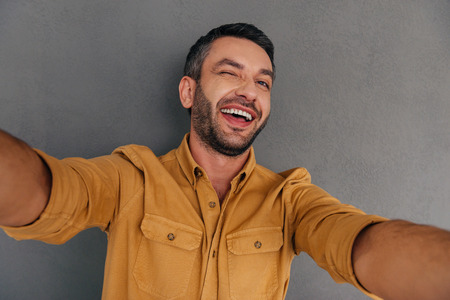 Selfie fun. Smiling young man making selfie and grimacing while standing against grey background