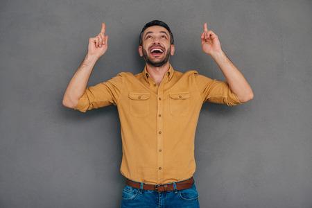 hombres maduros: Basta con mirar a eso! Hombre maduro feliz que apunta hacia arriba mientras está de pie contra el fondo gris