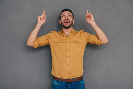 mature men: Just look at that! Happy mature man pointing up while standing against grey background