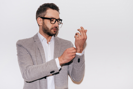 adjusting: Everything should be perfect. Confident mature man in smart casual wear adjusting his sleeve while standing against white background Stock Photo