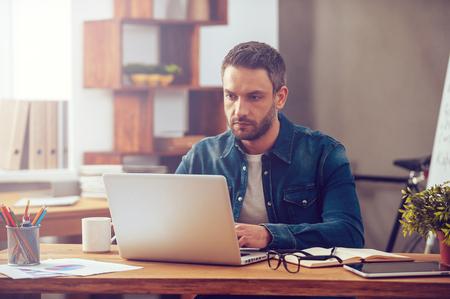 Concentrou-se no trabalho. Homem novo confiável que trabalha no portátil ao sentar-se no seu local de trabalho no escritório