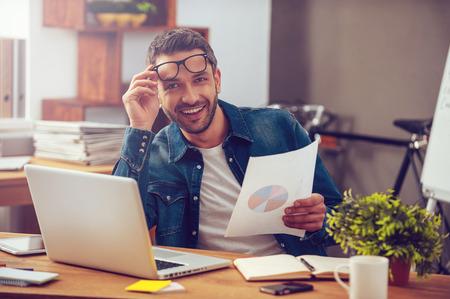 즉, 좋은 달이었다! 사무실에서 자신의 작업 장소에 앉아있는 동안 잘 생긴 젊은 남자 다채로운 그림과 종이를 들고 미소로 카메라를보고