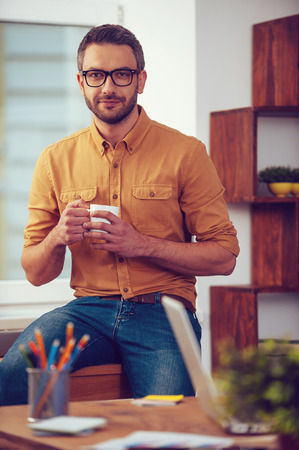 mature man: Enjoying hot and fresh coffee. Confident young man holding coffee cup and looking t camera while sitting at his working place in office