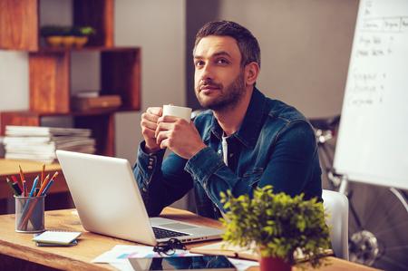 À espera de inspiração. Homem novo pensativo que prende o copo de café e desviando o olhar enquanto está sentado em seu lugar de trabalho no escritório