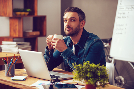 영감을 기다리고 있습니다. 사무실에서 자신의 작업 장소에 앉아있는 동안 사려 깊은 젊은 남자가 커피 잔을 들고 멀리 찾고