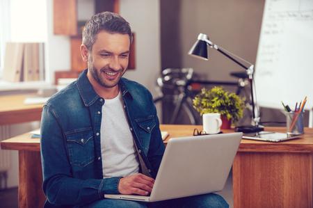사무실에서 인터넷 서핑. 자신감이 젊은 남자가 사무실에서 자신의 작업 장소에 앉아있는 동안 노트북에서 작동하고 미소