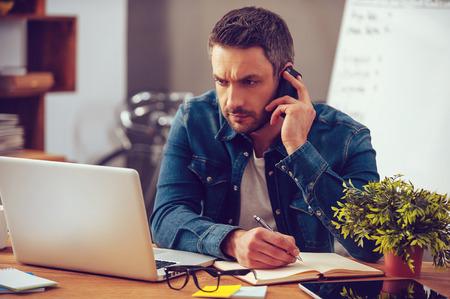 Tendo tanto trabalho a fazer. Homem novo confiável que trabalha no portátil e falando no telefone celular enquanto está sentado em seu lugar de trabalho no escritório