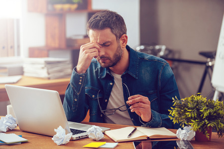 business person: Feeling sick and tired. Frustrated young man massaging his nose and keeping eyes closed while sitting at his working place in office Stock Photo