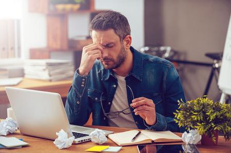 Sentir-se enjoado e cansado. Homem novo frustrante massageando o nariz e mantendo os olhos fechados enquanto está sentado em seu lugar de trabalho no escritório