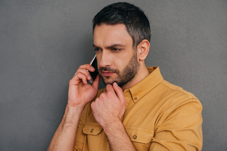 business casual: I need to think about it. Thoughtful mature man talking on the mobile phone and holding hand on chin while standing against grey background