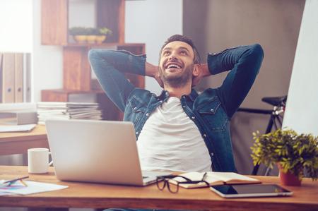 Tevreden met het werk. Gelukkig jonge man die op de laptop zittend op zijn werkplek in office Stockfoto