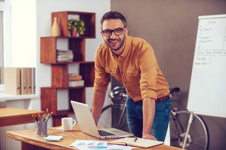 Confiante e bem sucedida. Homem novo considerável olhando para câmera e sorrindo ao estar perto de seu local de trabalho no escritório