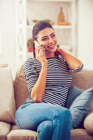 couch: Good talk with friend. Beautiful young woman talking on the mobile phone and smiling while sitting on the couch at home