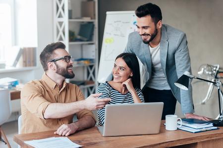 함께 해결책을 찾기. 사무실에서 책상에 앉아있는 동안 스마트 캐주얼웨어에 자신감 비즈니스 사람들의 그룹은 뭔가 논의