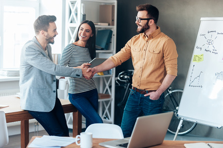 Good job! Confident young man standing near whiteboard and shaking hand to his colleague while young woman standing near them and smiling. Stock Photo