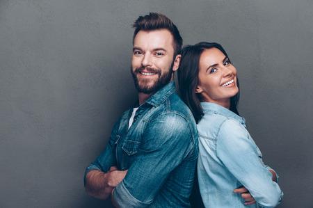 sexo pareja joven: Feliz pareja amorosa. Tiro del estudio de la hermosa joven pareja en jeans de pie espalda con espalda y sonriendo Foto de archivo