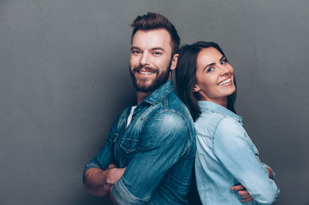 sex pose: Happy loving couple. Studio shot of beautiful young couple in jeans wear standing back to back and smiling